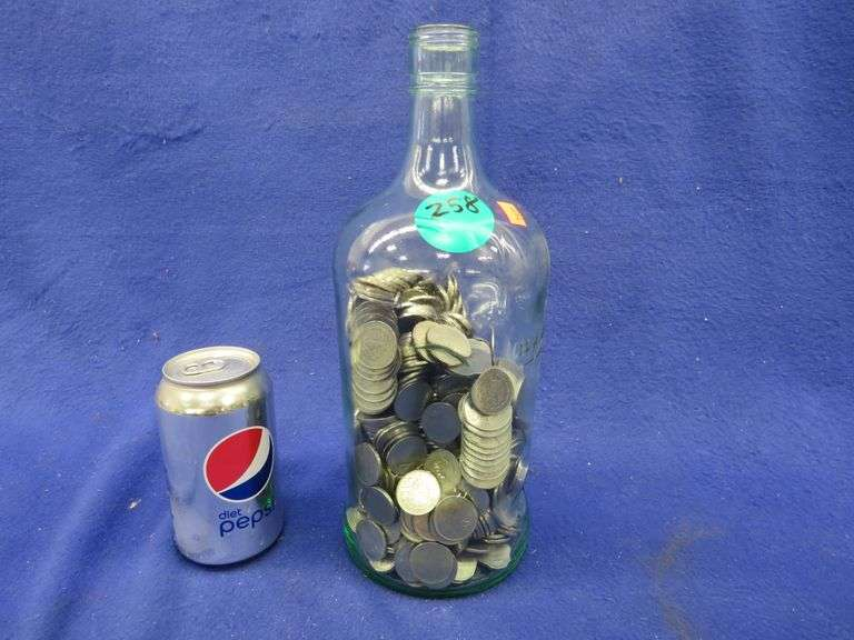 Large bottle 3/4 full of Mexican $1 coins.  Coins are worth approx. 5 cents each at current prices.