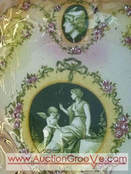 Antique porcelain biscuit jar with a cherub and Grecian woman. It is gold trimmed and has a metal cover and handle. The biscuit jar measures approximately 6.5 inches high not including the cover or handle.